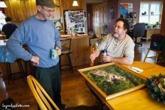 Roger Chaloux, left, and Hector Chaloux in Roger's house with an aerial photo of their wood yard when it was full of wood.