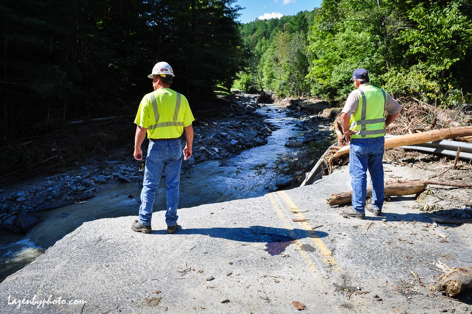 Workmen gaze into the gap where Camp Brook destroyed Camp Brook Road, Bethel, VT, one route into the town of Rochester.
