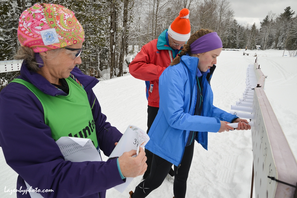Volunteers roll maps for the map exchange in the distance race at the International Orienteering Federation World Cup at Craftsbury Outdoor Center, Craftsbury, VT.